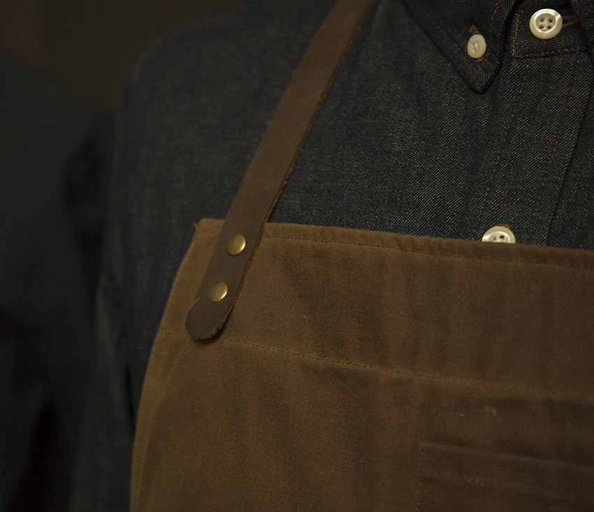 The Bond Street apron features leather straps sourced from Ohio and brass pieces from Massachusetts.