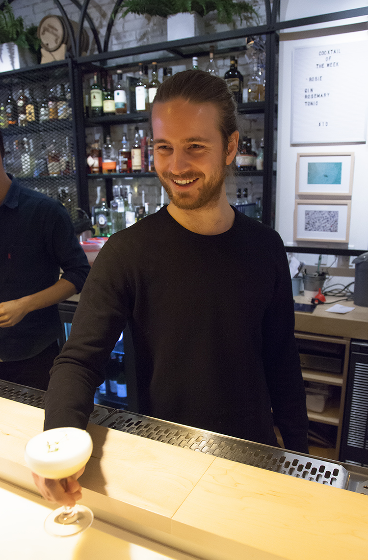 Giles stands at the bar, where they craft cocktails using fresh and seasonal ingredients.
