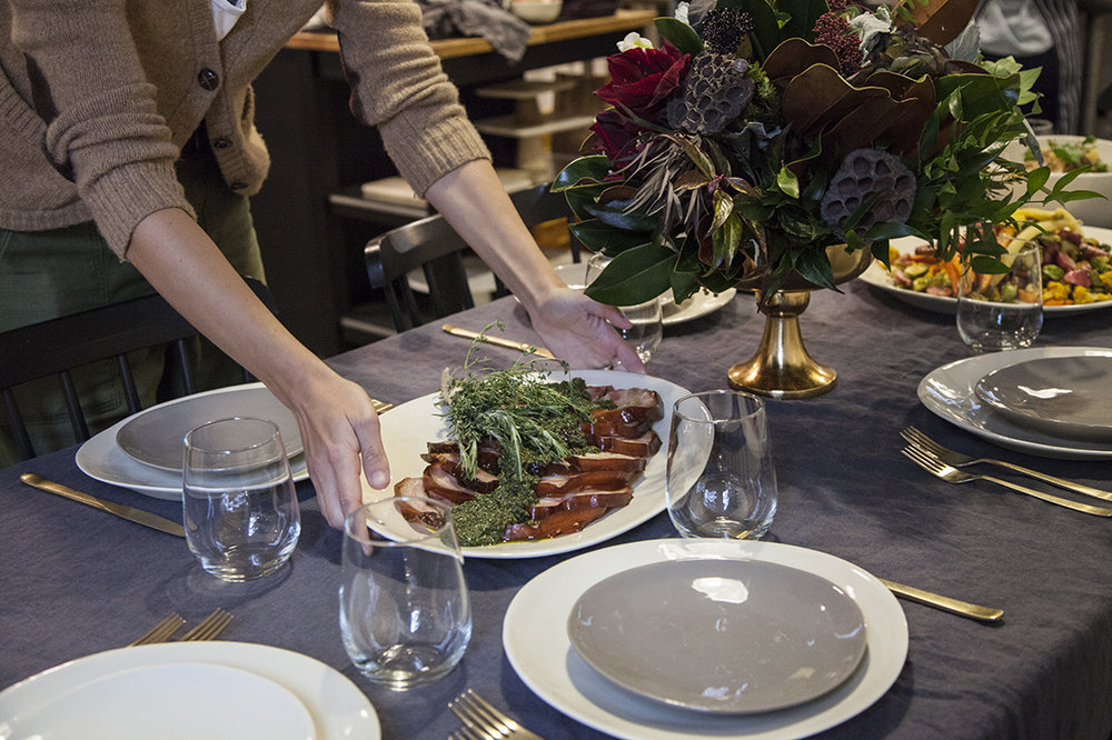 Jamie sets the table with a platter of porchetta - set on a glossy  white curved platter ,alongside matching  grey plates . Flower centerpiece courtesy of  Gotham Florist .