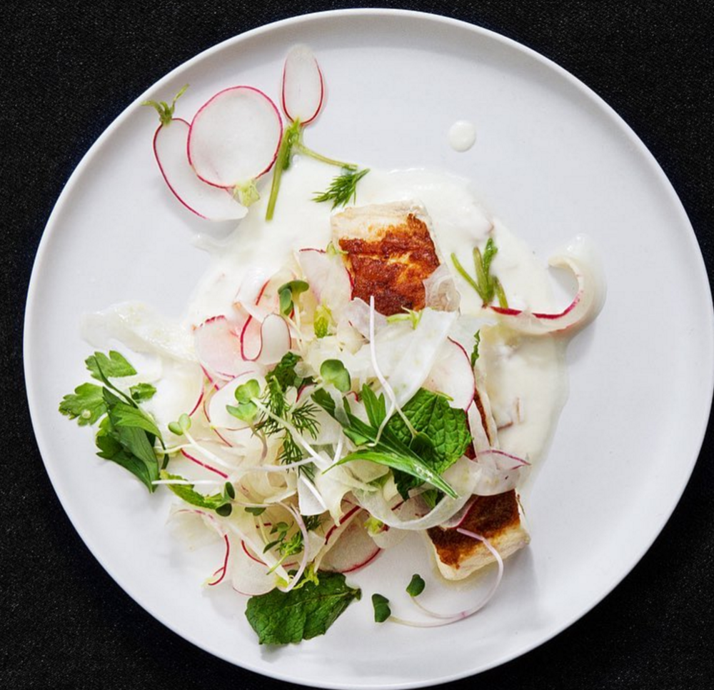 Striped bass with shaved fennel, radish and herb salad over preserved lemon raita.  [  Photo by Poppy's]