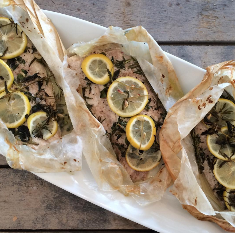 Snapper en papillote with lemon and herbs is served family-style in their parcels of parchment paper. [Photo by Poppy's]