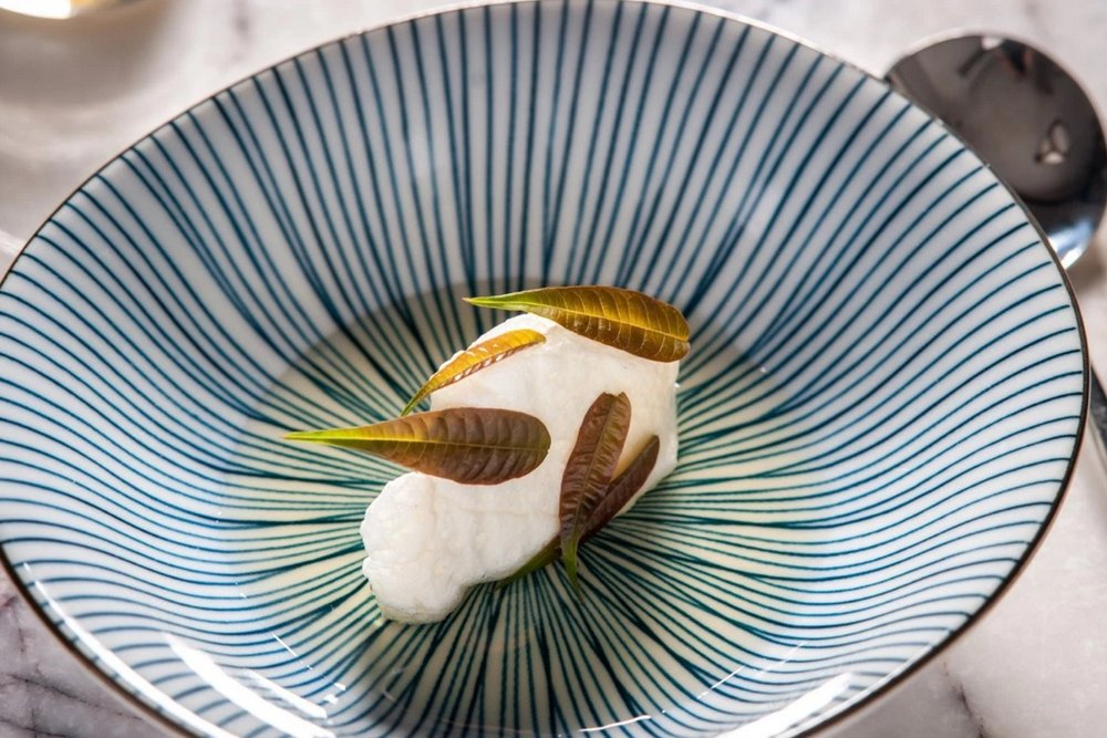 "Fung Tu's ""toon cloud"" dish is made with meringues poached in a light smoked fish broth, infused with star anise, ginger, garlic and scallion, topped with raw toon leaves.  [Photo by  Paul Wagtouicz]"