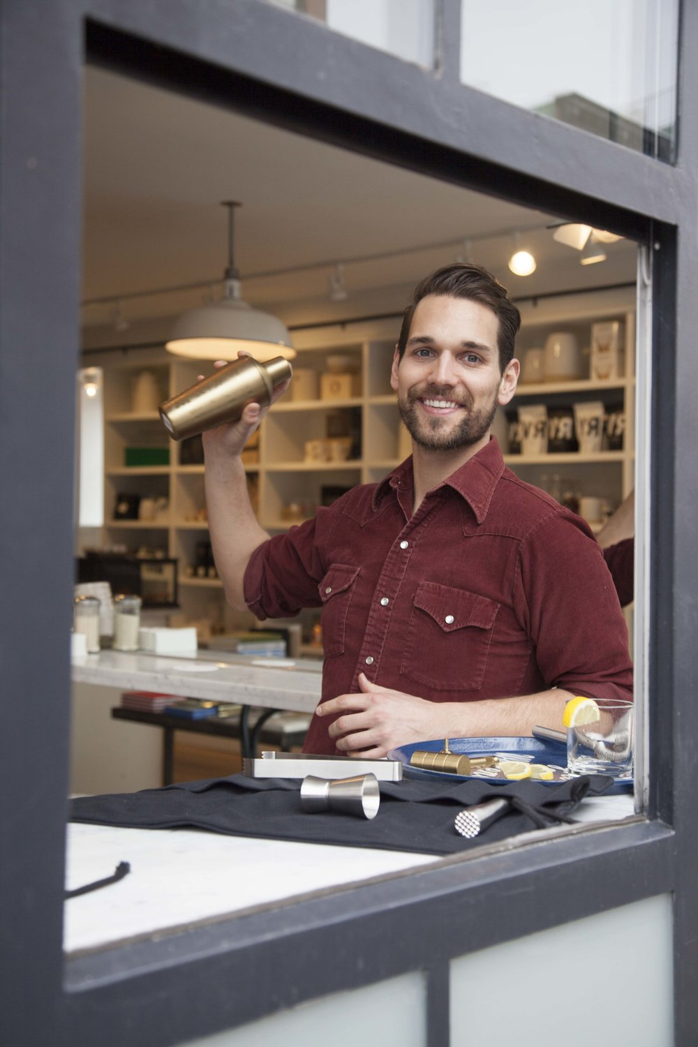 Dan Sorg, director of retail, mixes up a drink using Izola barware in the window of Regular Visitors.