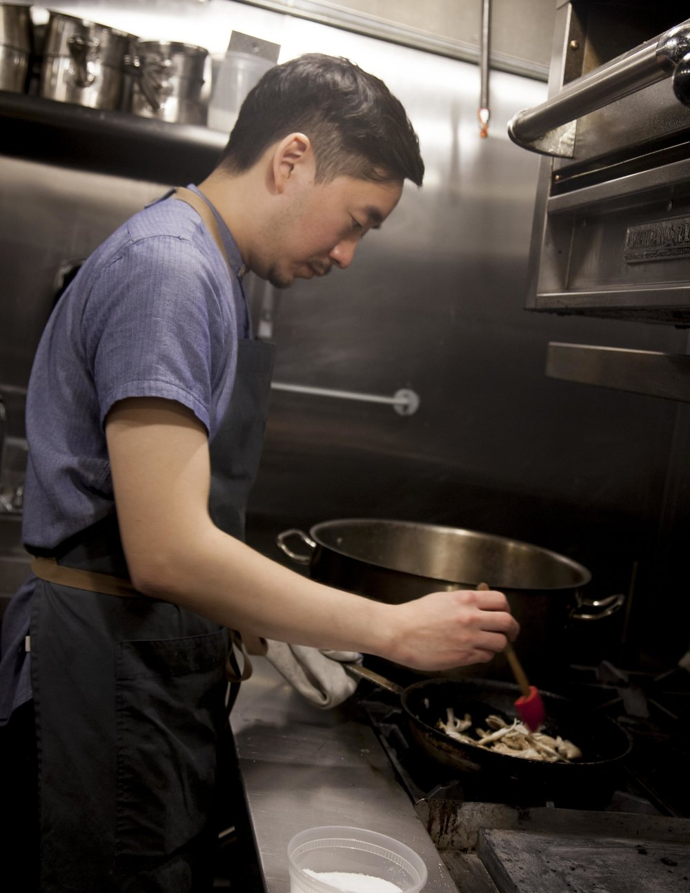 Chef Junghyun prepares a crispy sunchoke dish in his kitchen.