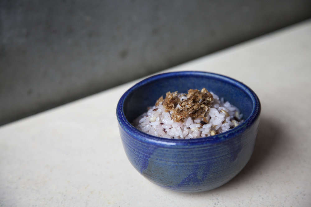 "Seven-grain rice topped with dried bonito flakes (""okaka"")."