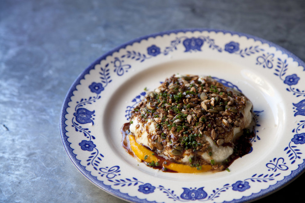 Butternut squash topped with stracciatella cheese, granola with herbs, and a vinegar reduction.