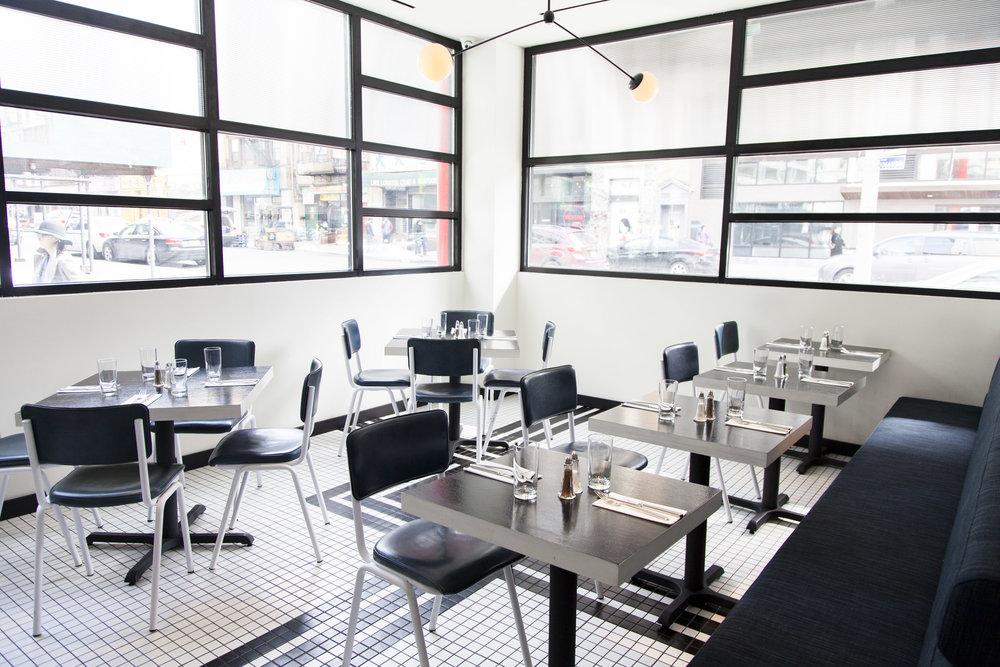 The sunlit back dining room of Nickel & Diner.