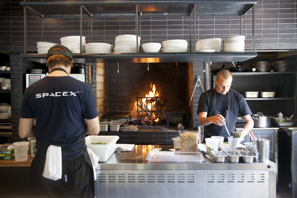 Metta's open kitchen has a custom fire-powered grill and griddle, vertical fire basket, wood fire-powered oven, and a stove top. No gas grills are used.