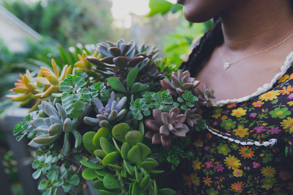 Dawn Owens of alevri Marketplace holding a bouquet of succulents by O'berry's succulents. Photography by Bridge + Bloom.