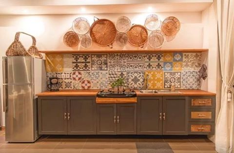 Hand woven baskets and Spanish style patterned tiles give the kitchen vibrant depth.  Link in bio.