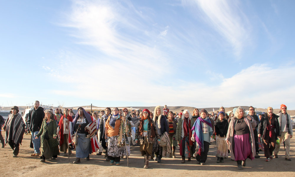 Women march through Oceti Sakowin Camp for a prayer ceremony at the base of Turtle Island. Photo by Tania Ellersick