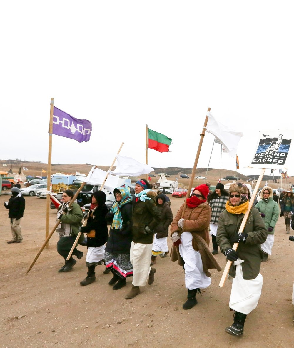 "Native women march through Oceti Sakowin camp carrying signs reading, ""Defend the Sacred"". Photo by Heather Wilson"