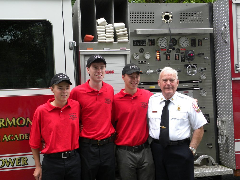 Curtis Lessard, Charlie Kelly, Michael Hirschbuhl stand with Woodstock retired Fire Chief Butch Sutherland at the vermont Fire Academy Cadet graduation.