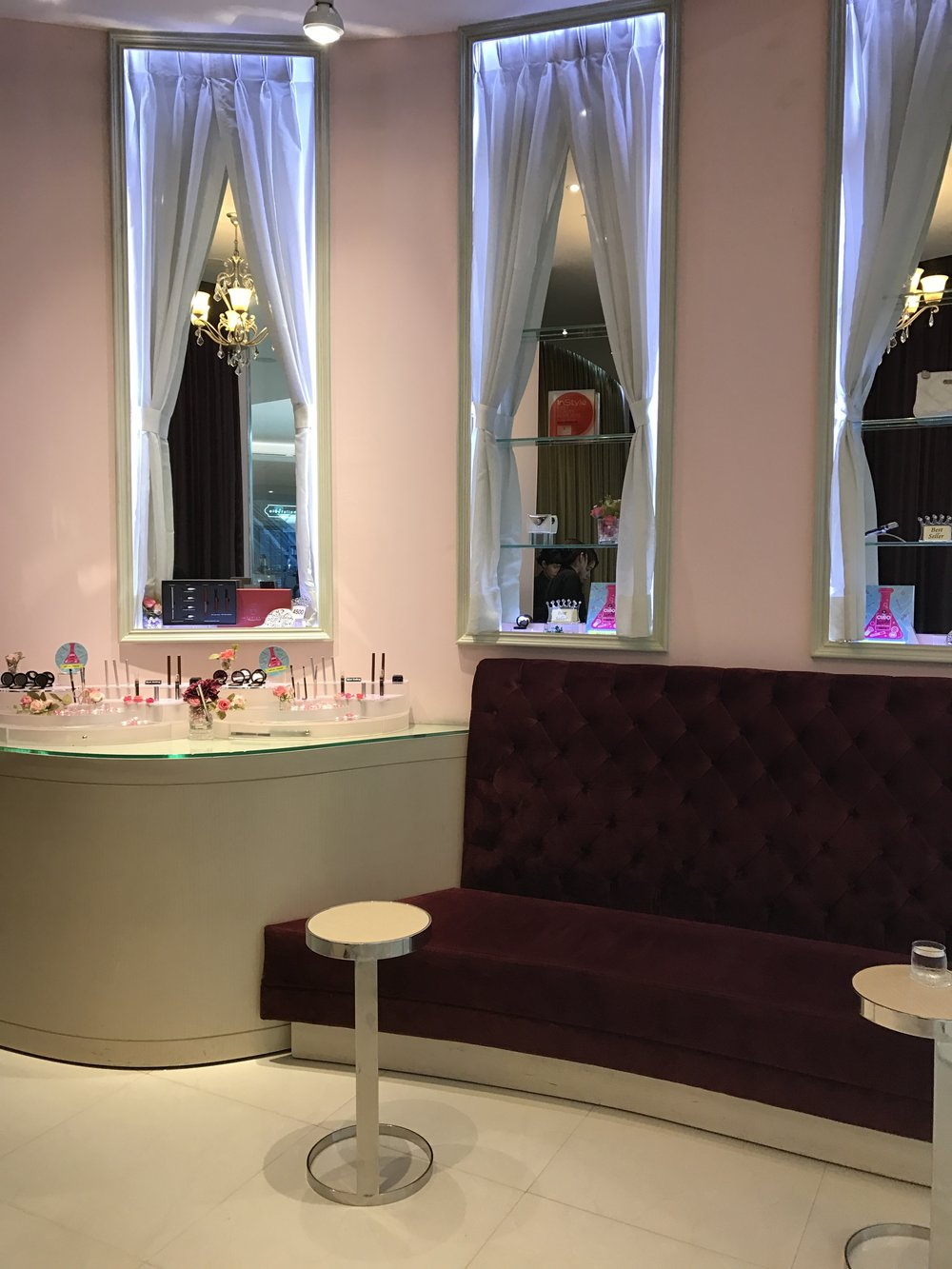 Plush purple sofas in the waiting area and a selection of their make-up products on the counter