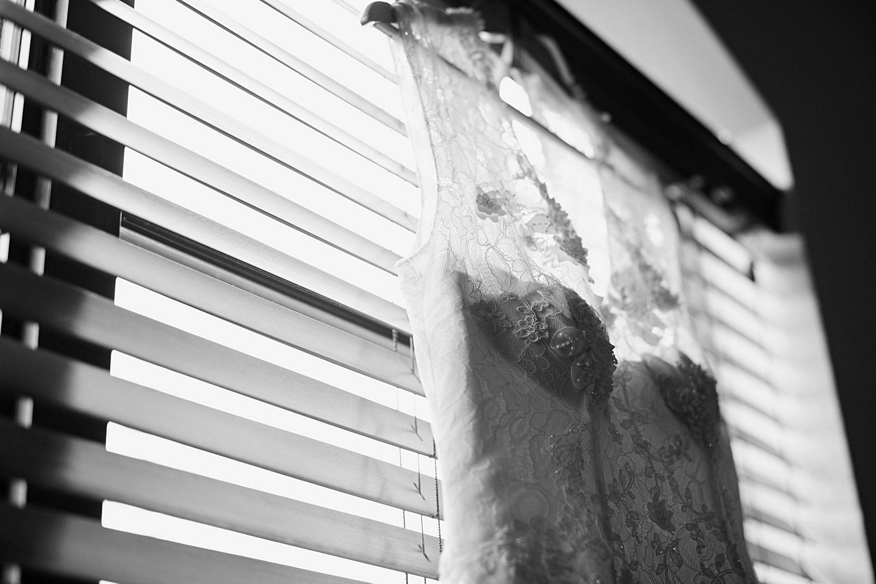 brides dress hangs in window