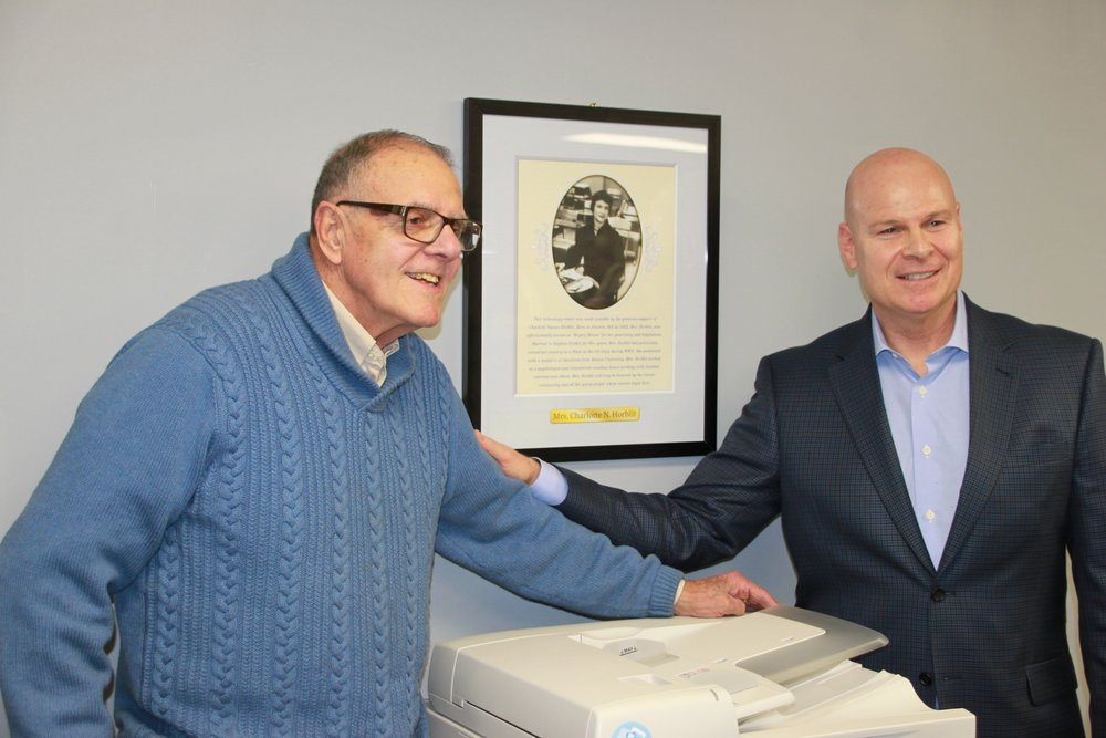 Carver board member, Dick Whitcomb, and Mark Feinberg, the benefactor who made the Charlotte Naomi Horblit Technology possible, standing before the portrait of the late Charlotte Horblit