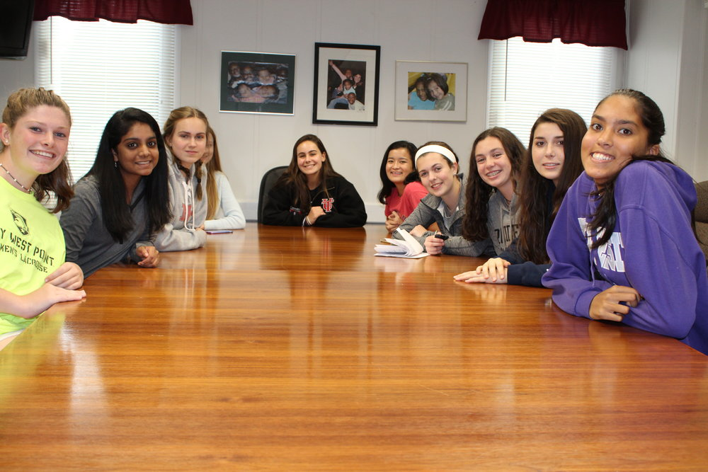 Kiera Russo is seated at the head of the table among her fellow volunteers from New Canaan High School