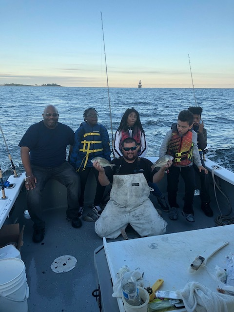 Brian Alert, Carver's Chief Program Officer, with four Carver students and the boat captain admiring the catch of the day!
