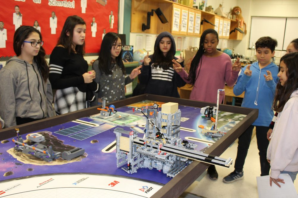 A team of students crossing their fingers a moment before they launch their giant robot into action to accomplish predetermined tasks — and their robot did all the tasks successfully!