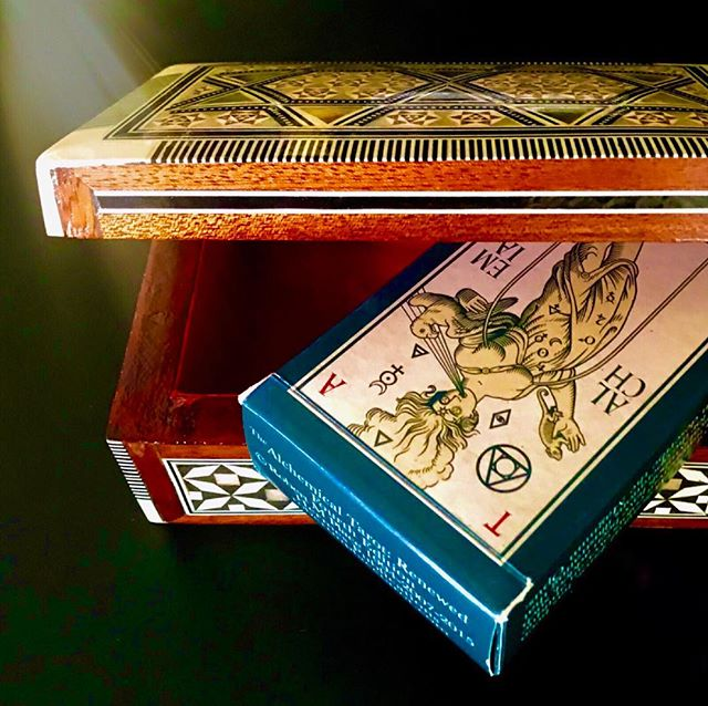 When using your active tarot decks, how you feel about your cards will affect your readings. I store my working decks in specifically paired boxes that reflect my energetic perception of the deck. 🔻 The handmade box pictured, which I discovered on the Greek island of Mykonos, is crafted of several woods, with a red velvet lining. Nearly every culture throughout history has attributed alchemical properties to wood.  Some hold one type of wood to be sacred, while others believe that all wood has magical properties.  Wood energy represents development, growth, and transition as does the tarot itself. 🔻 The red colored lining conveys vitality, excitement, action, and will. Red is associated with the first [root] chakra at the base of the spine and intends grounding the energetic physical body to the earth. This, for me, makes the combination of a wood and red vessel ideal for storing my Alchemical Tarot.