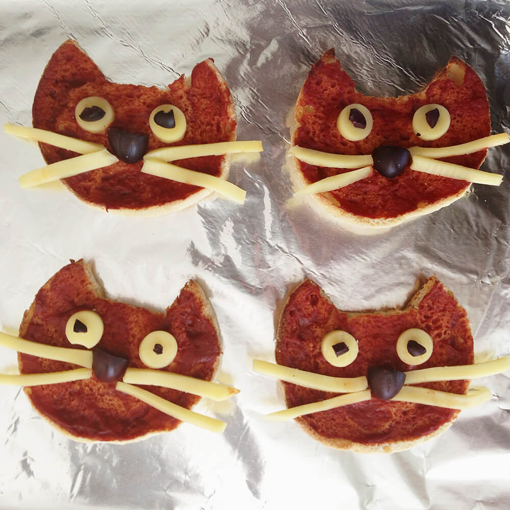We cut out cat shapes with English muffins to make cat pizzas!