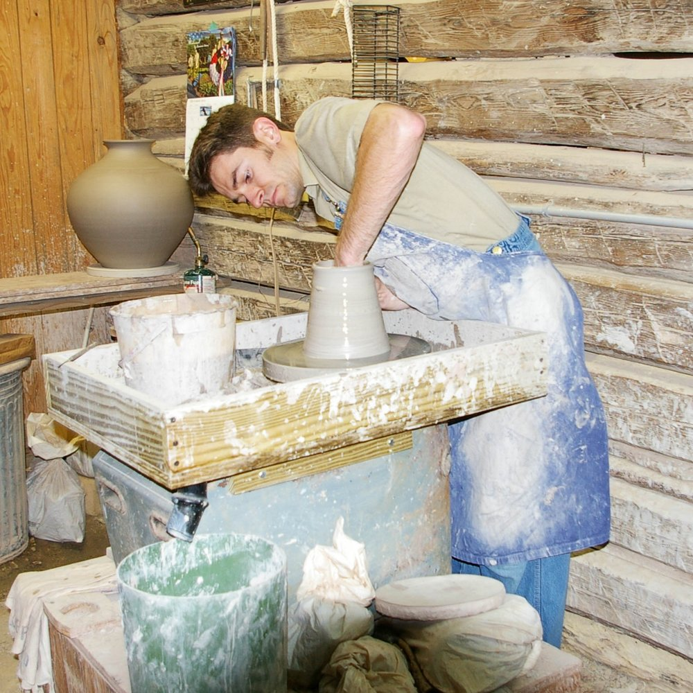 Travis Owens Turning a Pot at Jugtown Pottery.jpg
