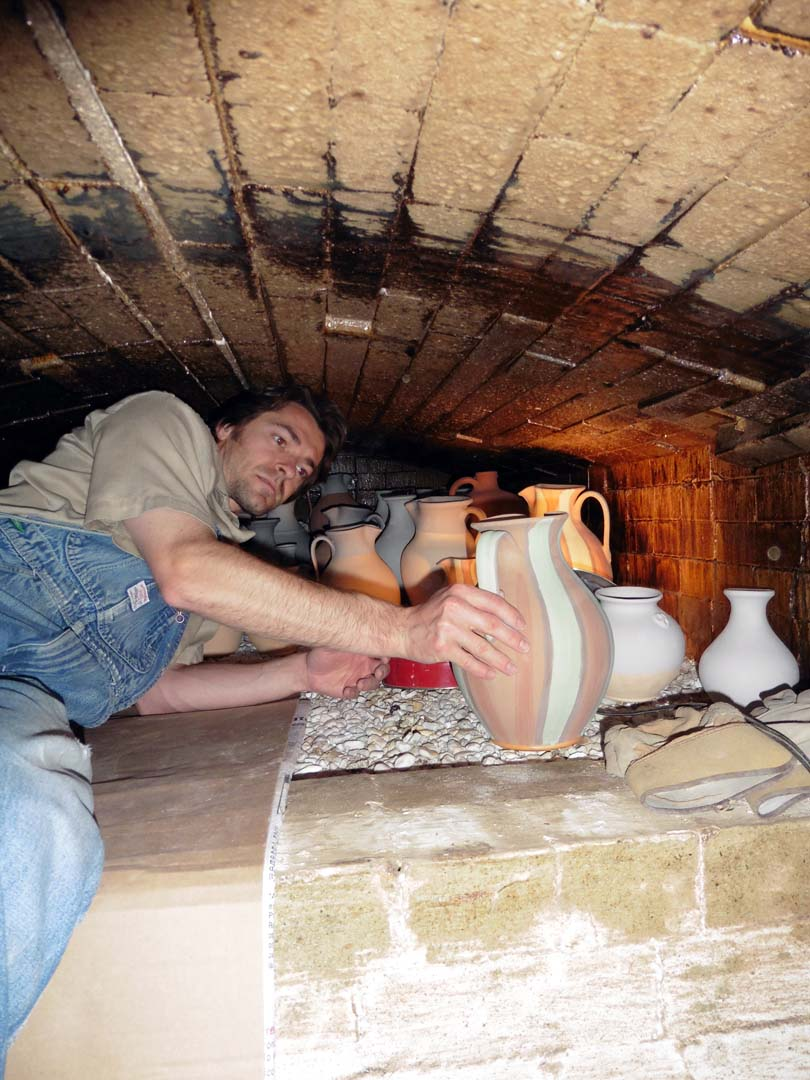Travis in the wood kiln placing the pots on crushed flint rock for a salt glaze firing