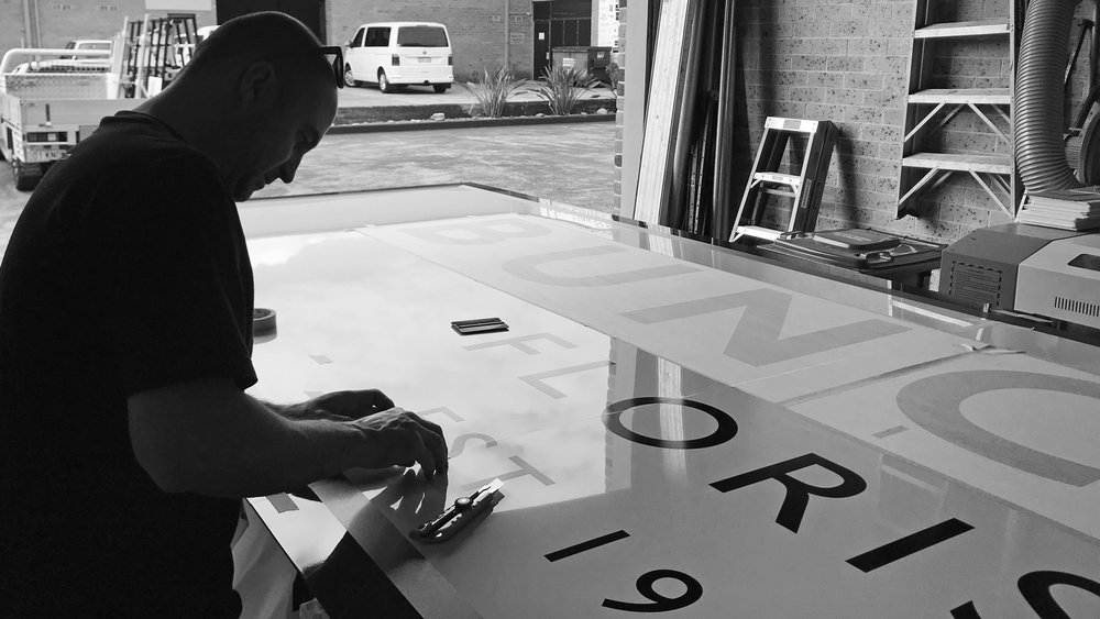 Applying graphics to signage panels in the workshop