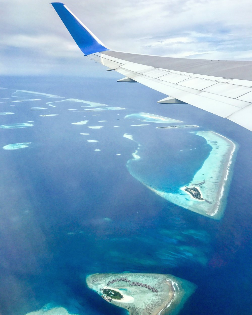The view flying into the Maldives is divine - travel in shoulder seasons for the best flight & accommodation deals!