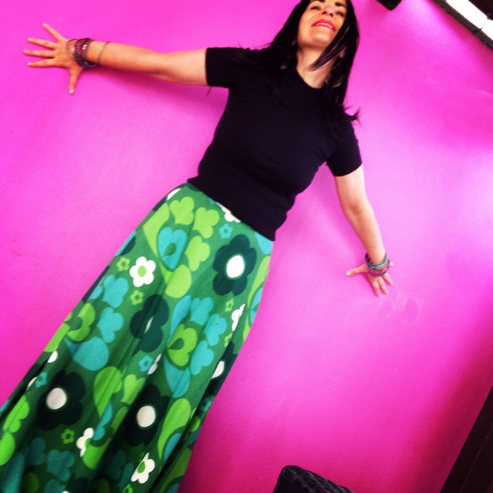 A pink garden wall location . This is a very striking combo as the pink and 60s green psychedelic print of the skirt are broken up by the black colour block crew neck balancing out the shot.