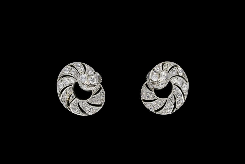 An ingenious pair of late 1930's pierced openwork Art Deco diamond swirl earrings set   £9257
