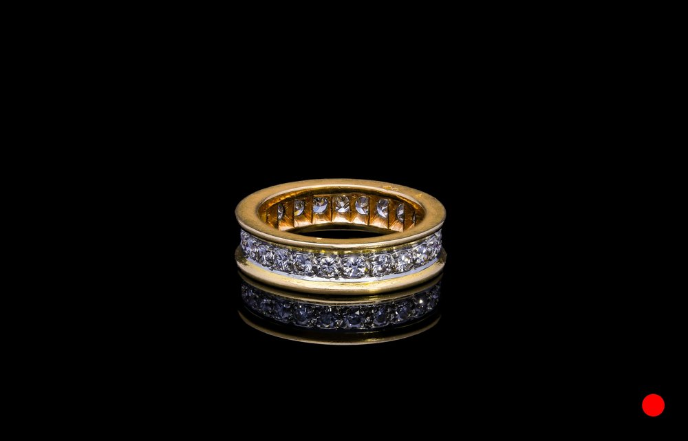 A French 1940's platinum and 18ct rose gold transitional round brilliant cut diamond eternity ring   £3250