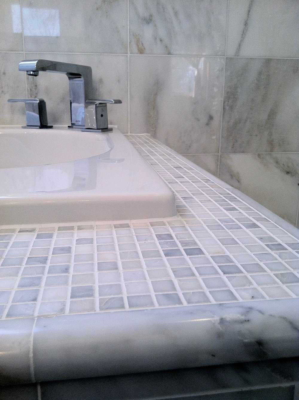 A modern sink fixture, beside marble wall tiles