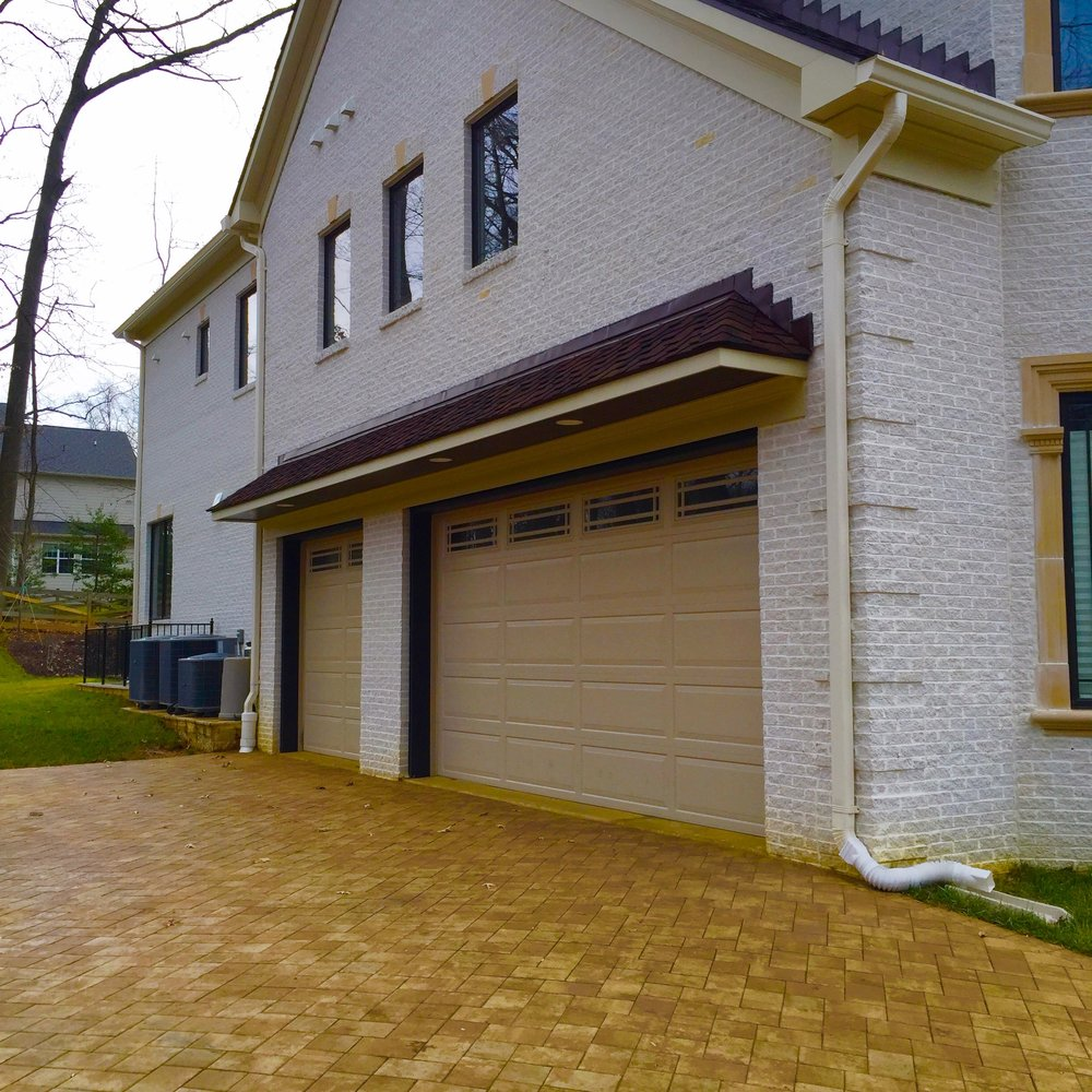 Earth-colored tiles pave this driveway to the double garage