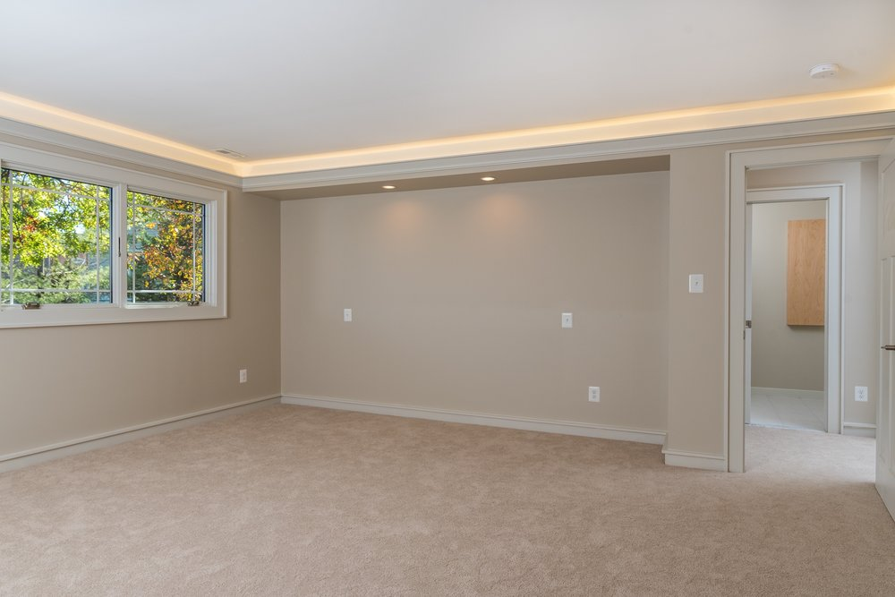 This remodeled bedroom includes natural, direct, and indirect lighting