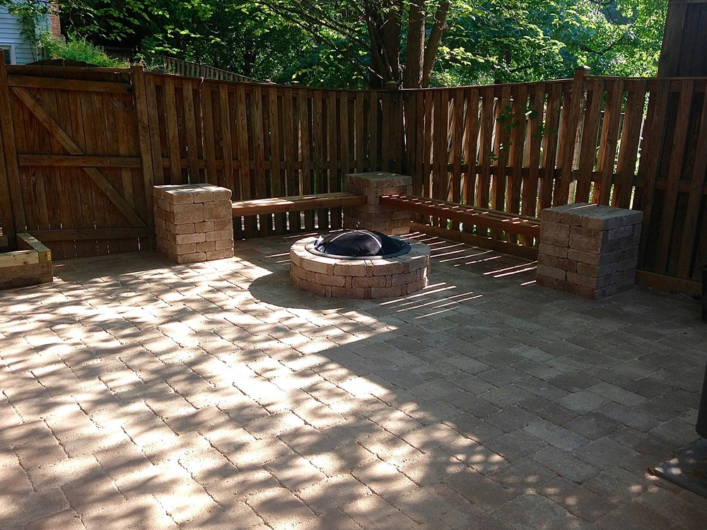 A backyard patio, featuring seating around a fire pit