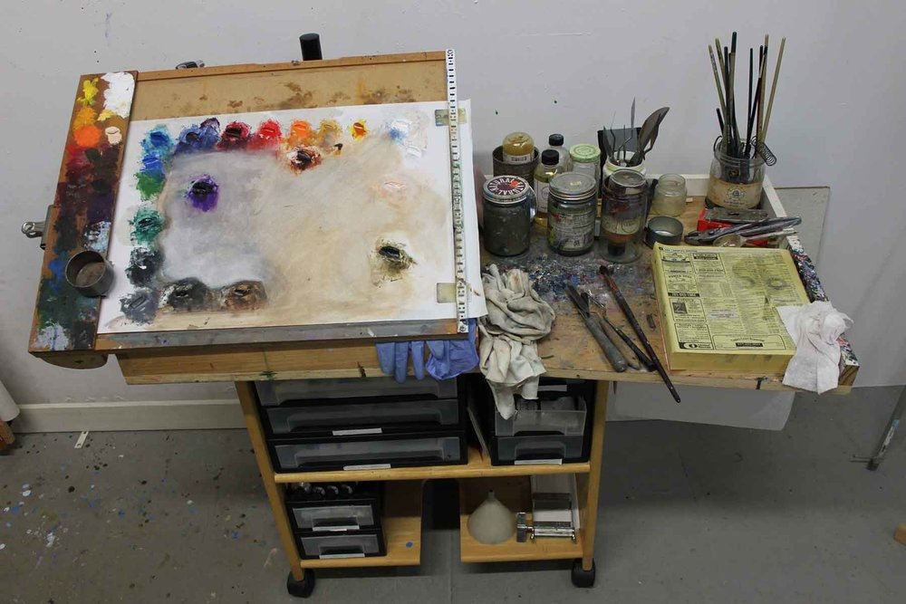Your book and blog also encouraged me to take a second look at my studio painting set up. After working in carpentry for six years, I've cobbled together all of my own studio furniture, and I felt confident to try to adapt some of your designs into a new taboret. This unit has been through a few configurations, but it's basically a custom upper section on top of a converted shelf on casters. I've installed drawers for paint below, and the kind of angled palette you use on top. One trick I picked up from school was to use an old phone book as a nearly endless wiping surface for unneeded paint. 'Works great.