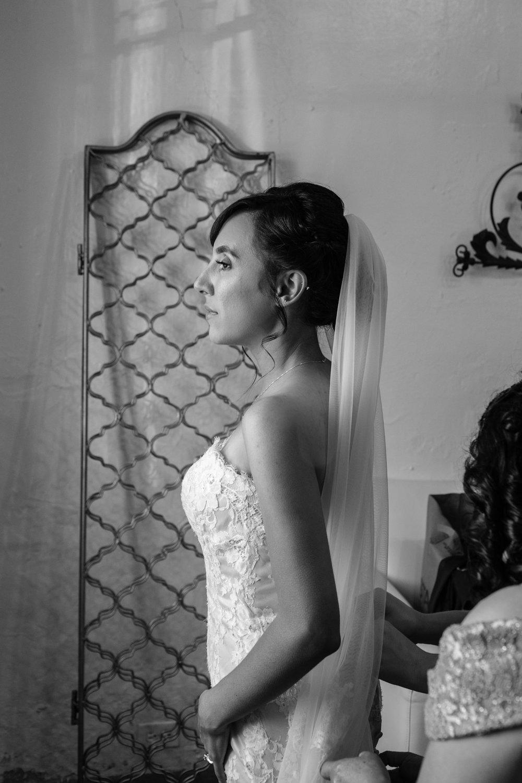 Bride putting on dresss