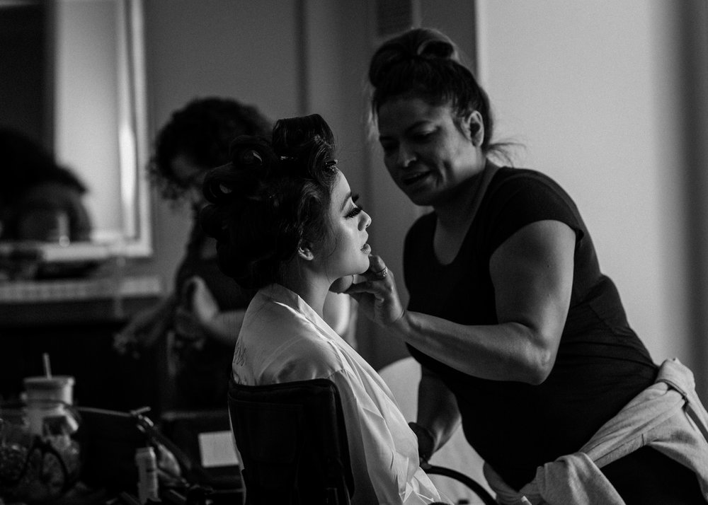 Bride getting makeup done black and white