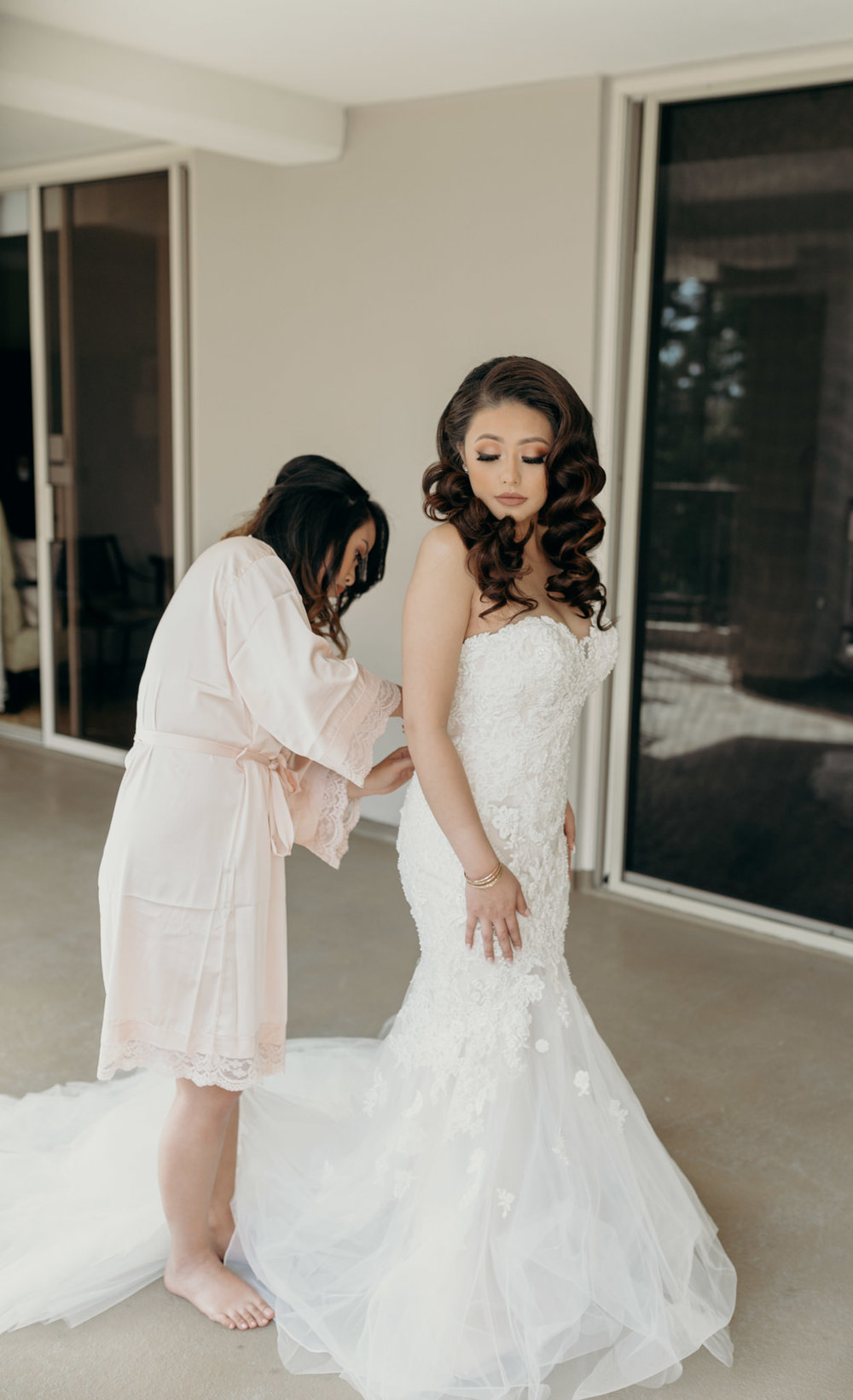 bride getting help into dress