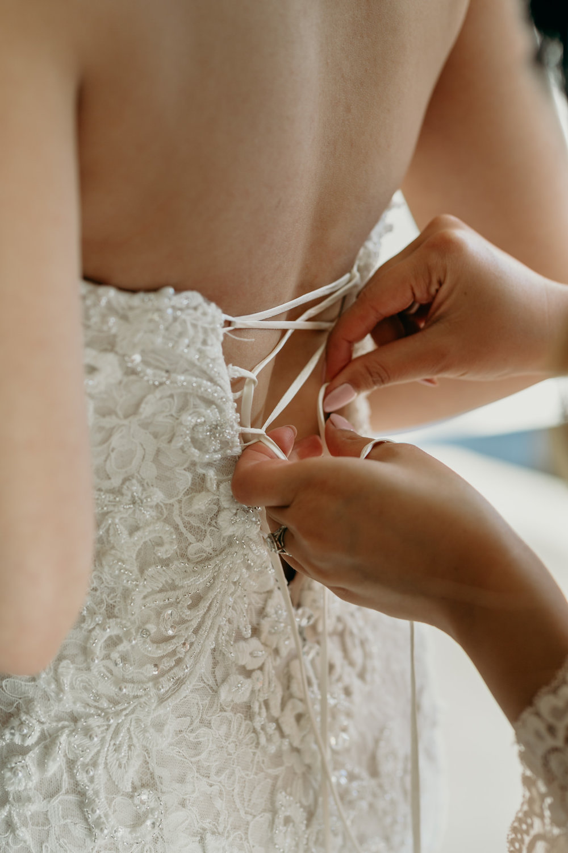 bridesmaid helping bride into dress
