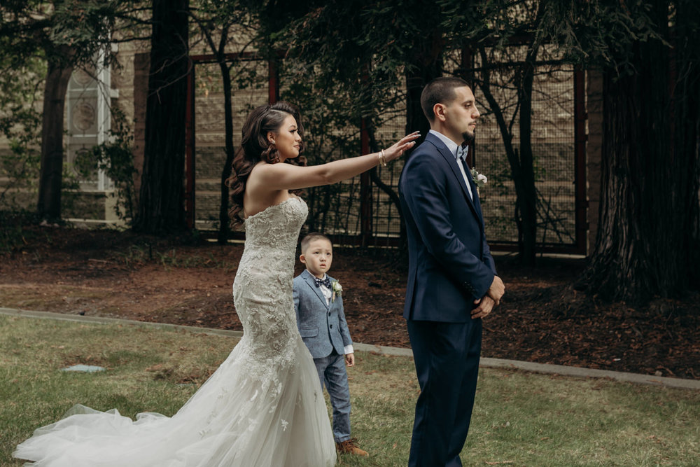 bride tapping groom shoulder for first look