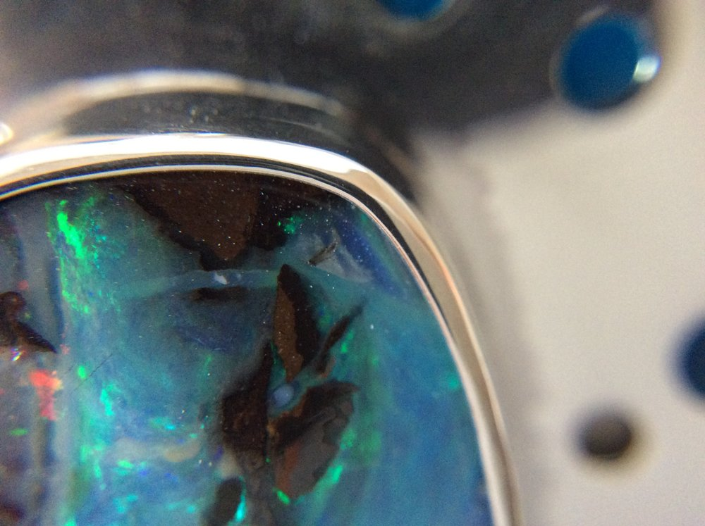 Close up of sterling silver, boulder opal & cold enamel pendant