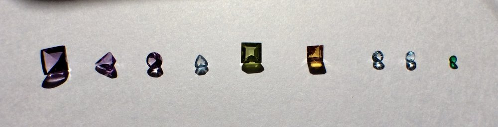 From Left to Right: Buff Top Square Cut Amethyst; Kite Shape Amethyst; Round Cut Amethyst; Trillion Cut Aquamarine; Square Cut Peridot; Princess Cut Citrine; Round Cut Sky Blue Topaz; Round Cut Swiss Blue Topaz; Round Cut Emerald