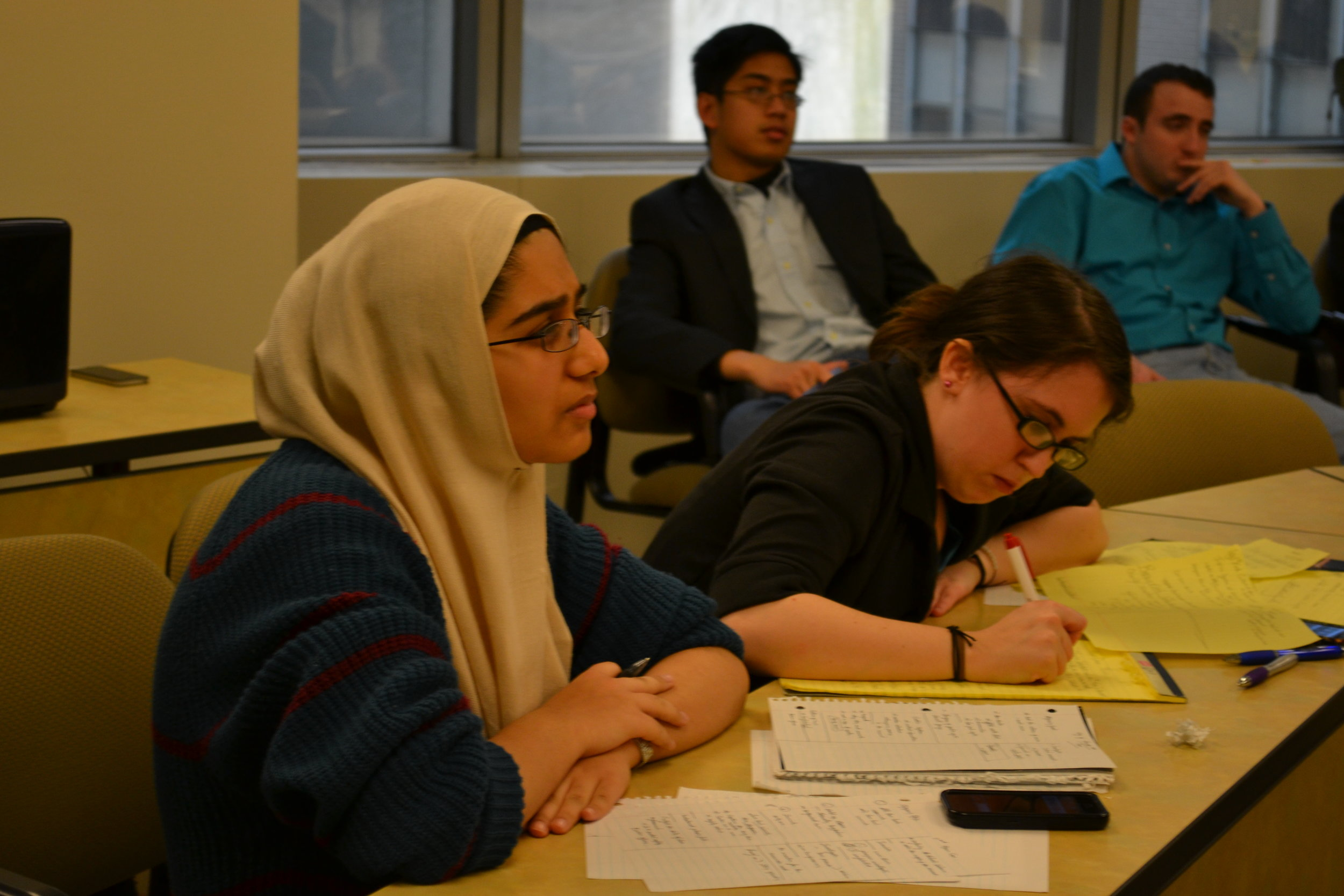 Colleen Fasone (right) and Ameena Rahman (left) from Adelphi University debate in the semi-final round. Photo courtesy of KDS.