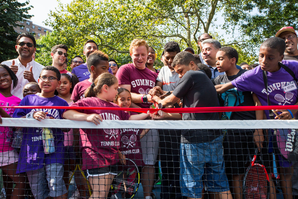King's County Tennis Leagues' students, friends, and family cut the second of two ribbons.
