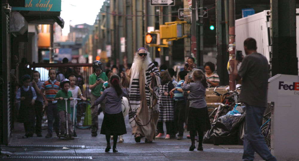 Dennis Gronam, dressed as the Messiah, strolls through Brooklyn guiding a white donkey | Photo courtesy of Messiahsez Facebook