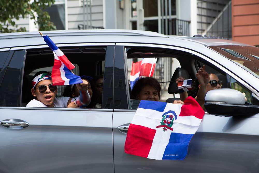 A Dominican family waves flags out the window of their suburban accompanying the 18th annual Williamsburg Dominican Parade, on Sunday, Aug 26, in New York. Photo: Wes Parnell