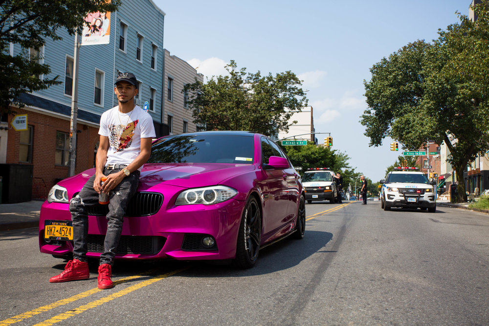 Victor Rivas poses for a photo with his souped up BMW as he tails up the last of the 18th annual Williamsburg Dominican Parade, on Sunday, Aug 26, in New York. Photo: Wes Parnell