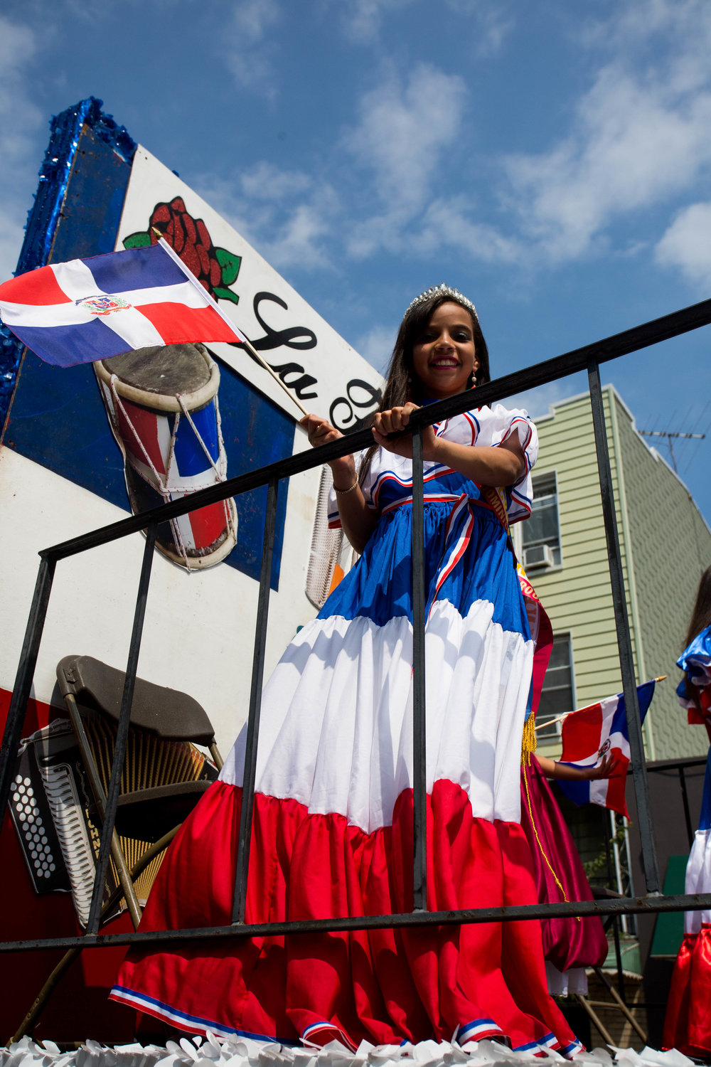 "A young beauty pageant participant waving a Dominican flag from the ""La Flor"" float at the 18th annual Williamsburg Dominican Parade, on Sunday, Aug 26, in New York. Photo: Wes Parnell"